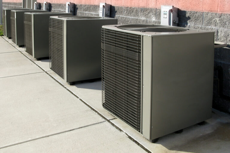 Row of commercial air conditioner compressor units near an industrial building