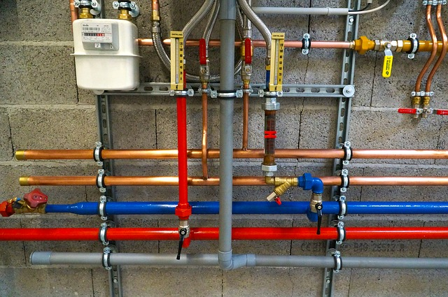 Copper, red, and blue water pipes against concrete wall