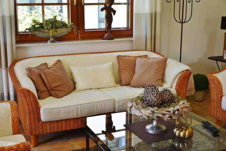 Wicker sofa with white cushions