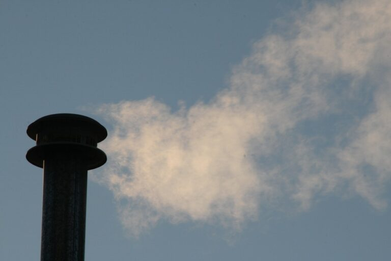 Chimney billowing smoke against blue sky