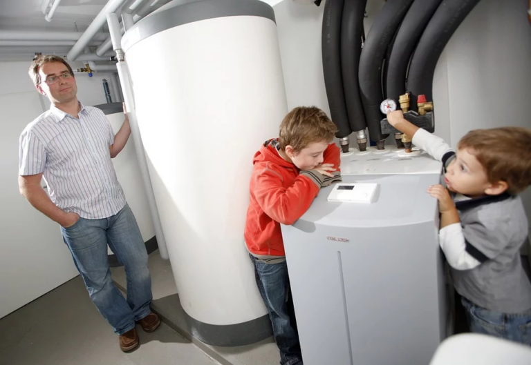Two boys looking at a heat pump supervised by their father