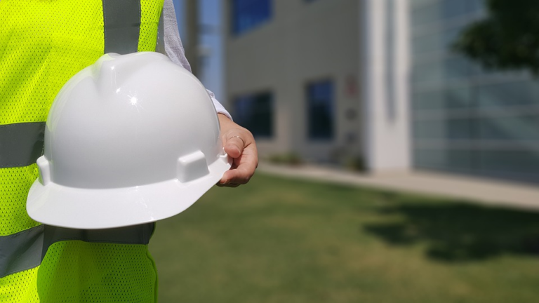 Worker in safety vest carrying white hard hat