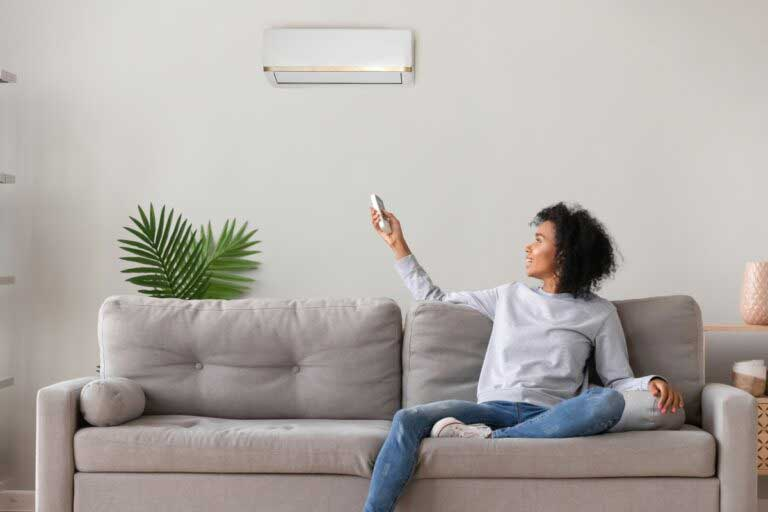 person sitting on couch using new air conditioner on wall