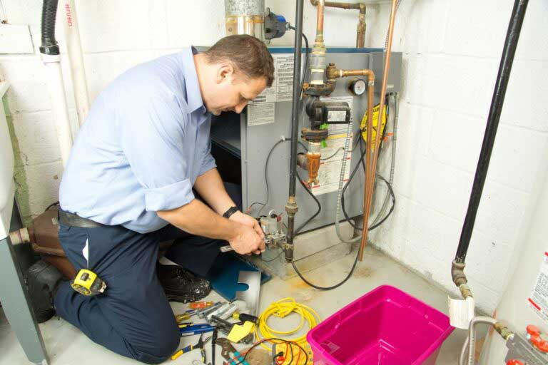 repair person fixing heating system in edmonton home